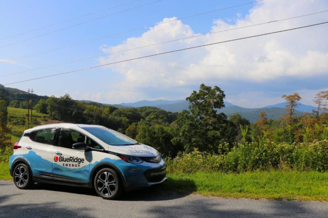 """Electric vehicle with """"Blue Ridge Energy"""" on the side parked in front of a scenic mountain view."""