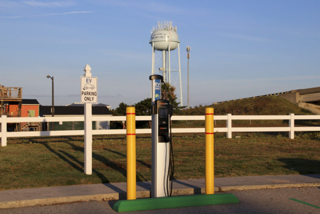 """Electric Vehicle charging station in front of water tower that reads """"Welcome to Holden Beach"""""""