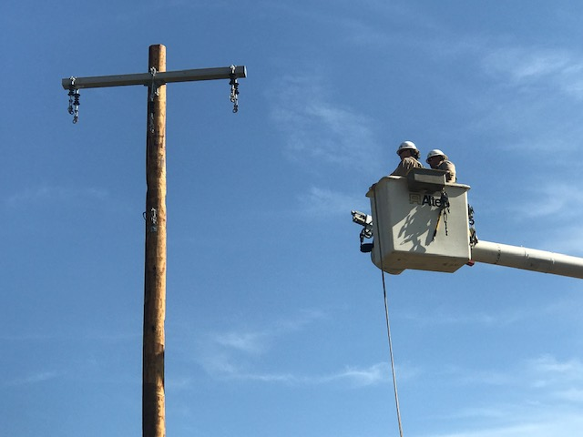 Two adults in a bucket truck as the bucket is being raised to a utility pole.