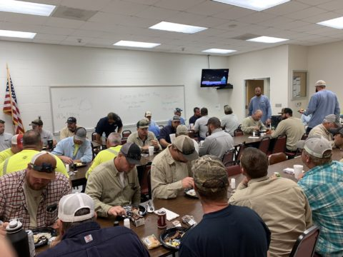 Crews in a room, eating and getting ready to work