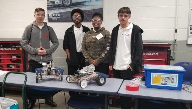Students standing with robotics equipment