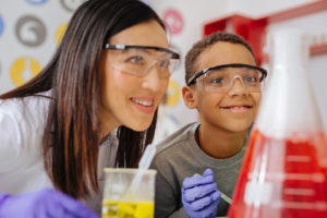 Teacher and student working on science experiment